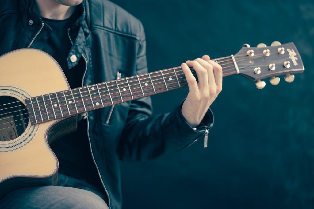 アコースティックギターを弾く少年