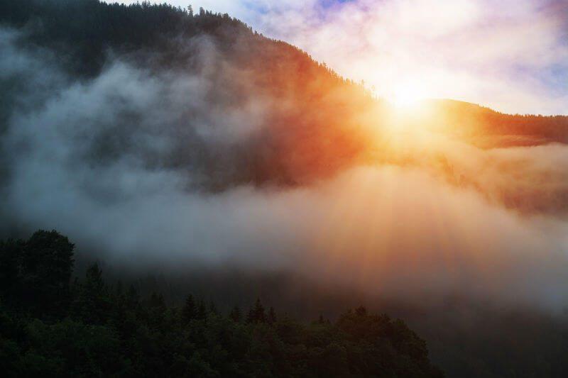 山の後ろから照らす日